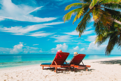dwa leżaki na tropikalnej wyspie nad morzem