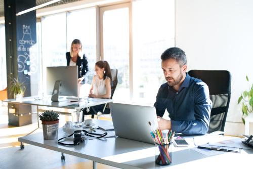 dwie kobiety i mężczyzna wykonujący pracę w biurze