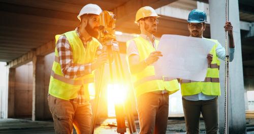 trzech mężczyzn geodetów wykonujących pomiary geodezyjne