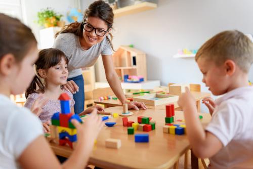 dzieci bawiące sie klockami z przedszkolanką