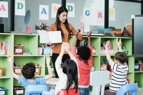 nauczycielka z dziećmi w przedszkolu pokazująca książkę