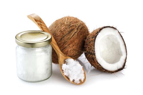 kokos z drewniana łyżką i słoikiem oleju kokosowego na białym tle