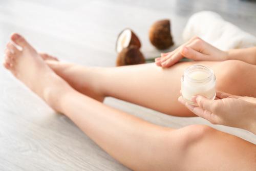 kobieta nakładająca olej kokosowy na nogi